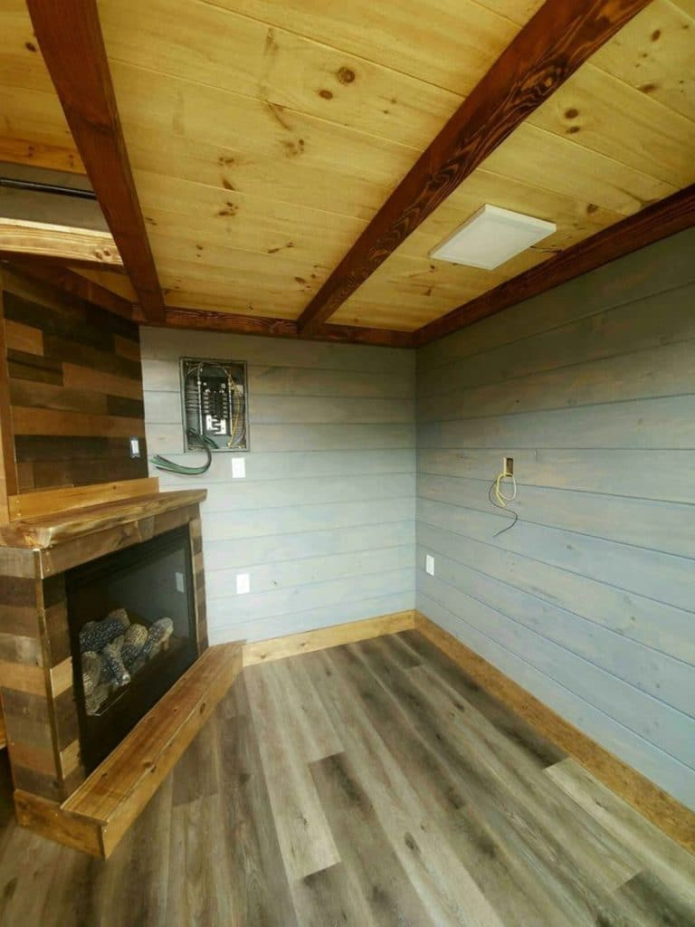 Living room with reclaimed wood flooring and shiplap wall