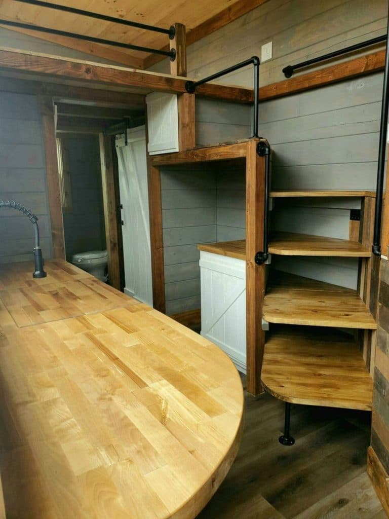 View of wooden stairs to loft and wooden countertop in kitchen