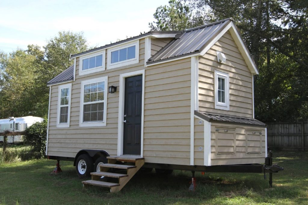 Front of tiny home with cream siding and white trim