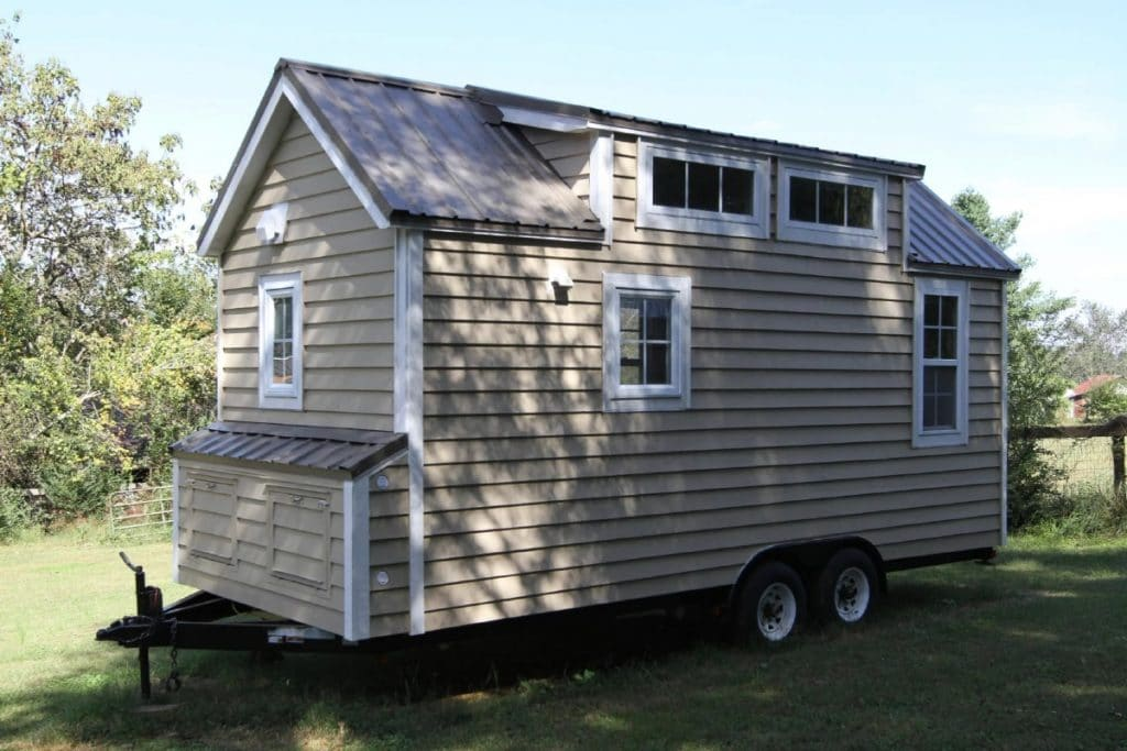 Back side of tan and white tiny house on wheels