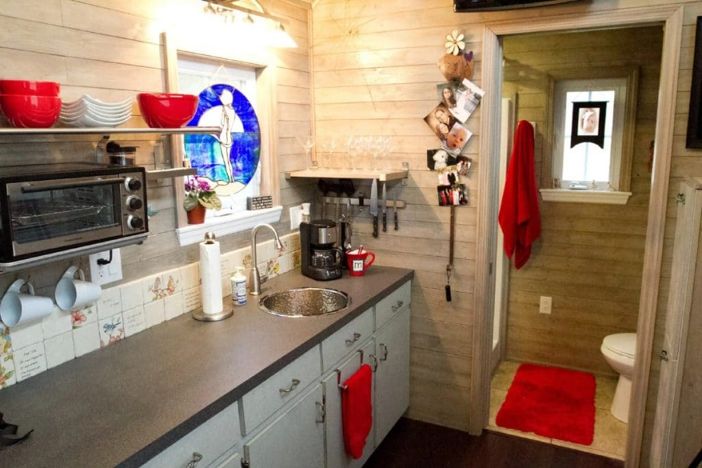 Kitchen counter against natural pine walls with red dishcloths