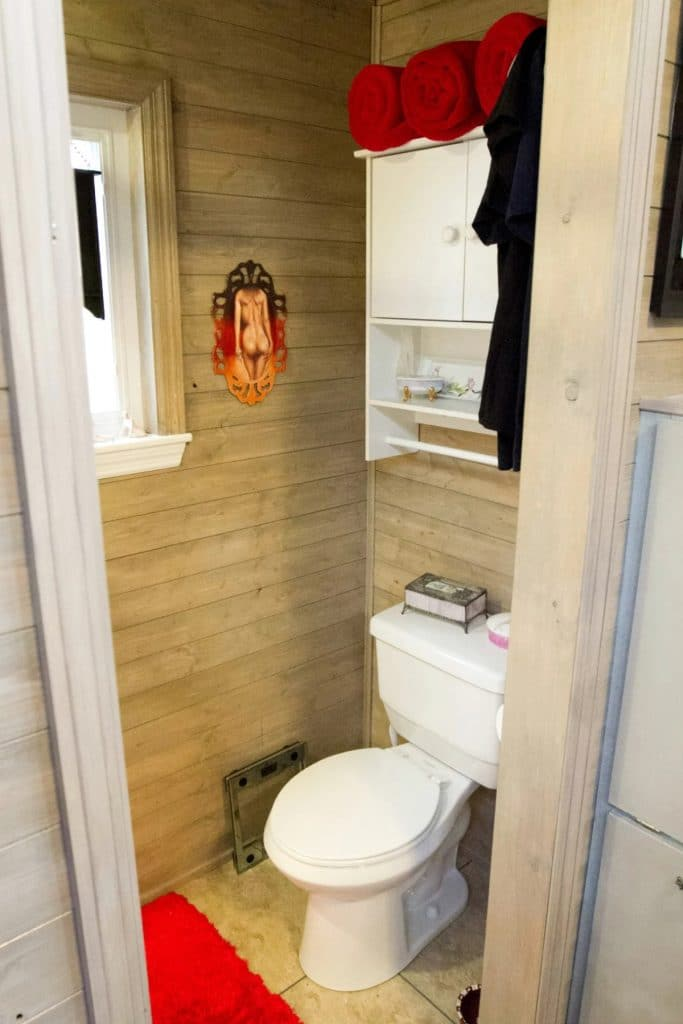 White toilet and cabinet against natural pine walls