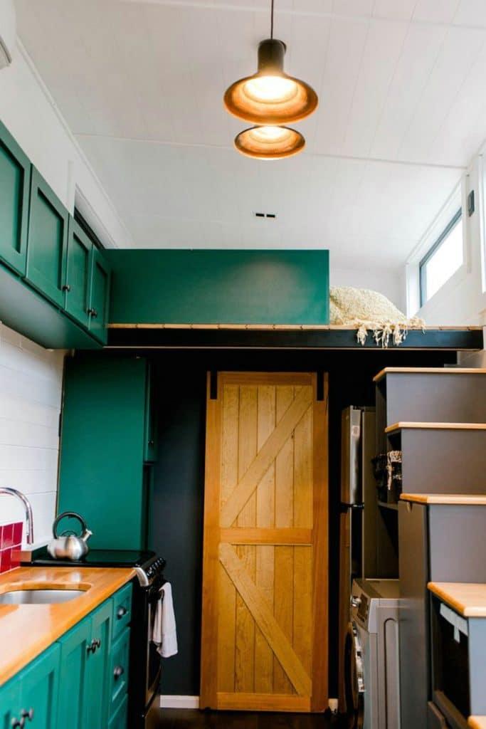 Light wood barn door past kitchen