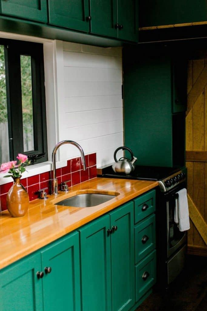 Butcher block countertop over green cabinets
