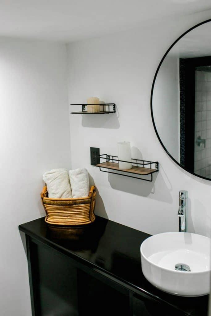 Bathroom vanity with dark wood counter white sink and basket of towels