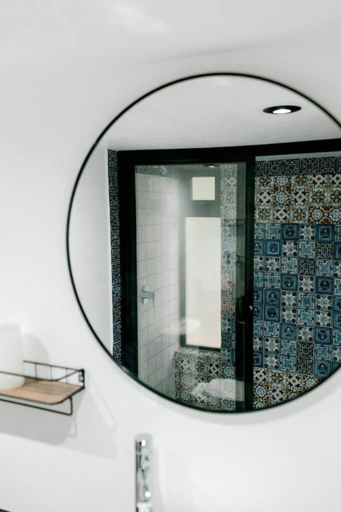 Round mirror on wall reflecting tile