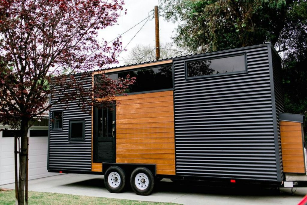 Black and brown tiny house in driveaway