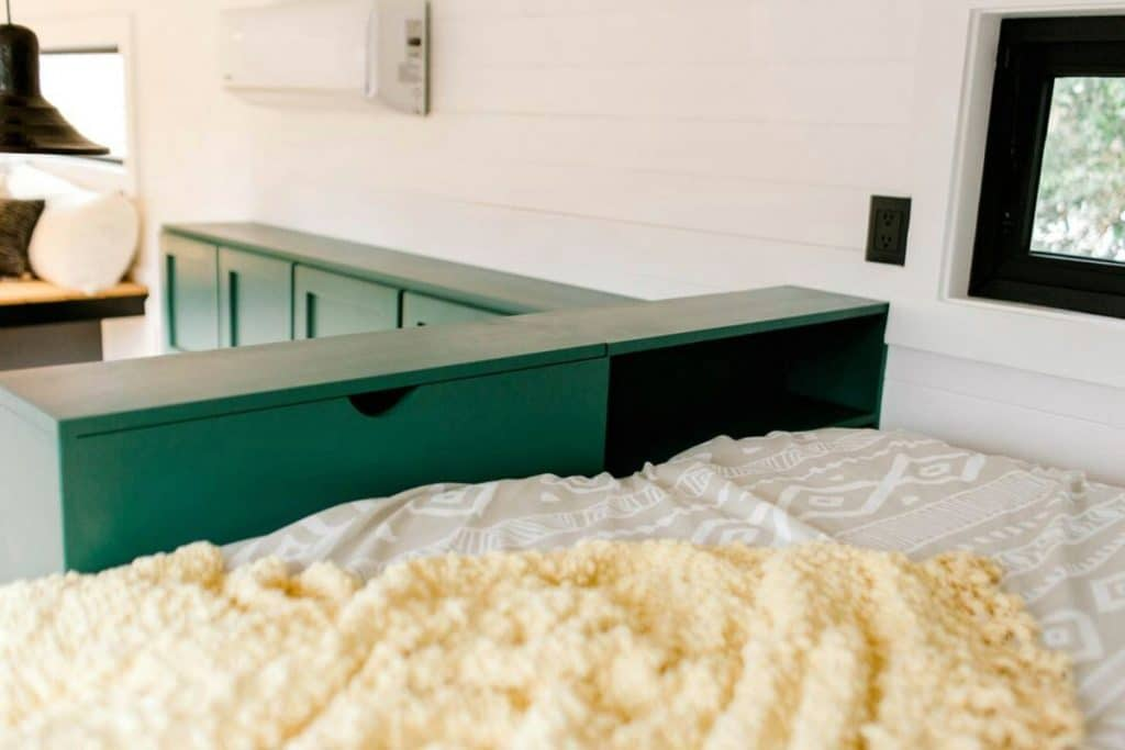 View of bed in tiny house loft with green drawers at wall
