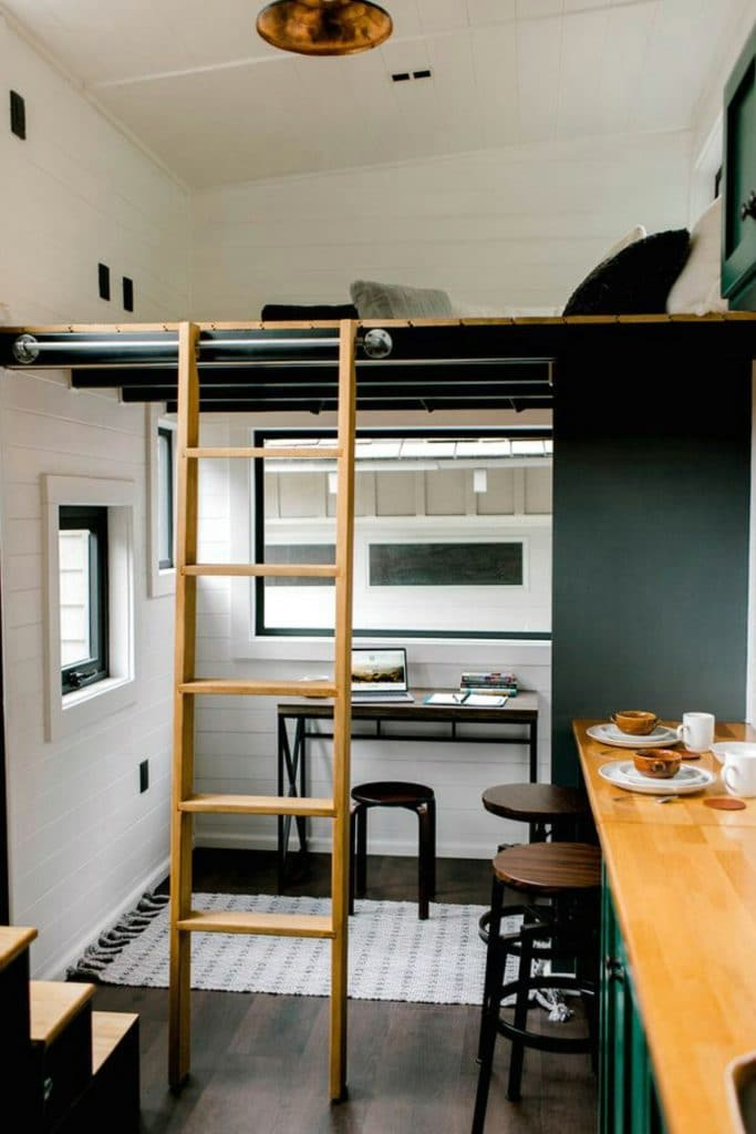 Wooden ladder leading up to small loft over office