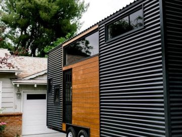 Side of black tiny house parked in driveway