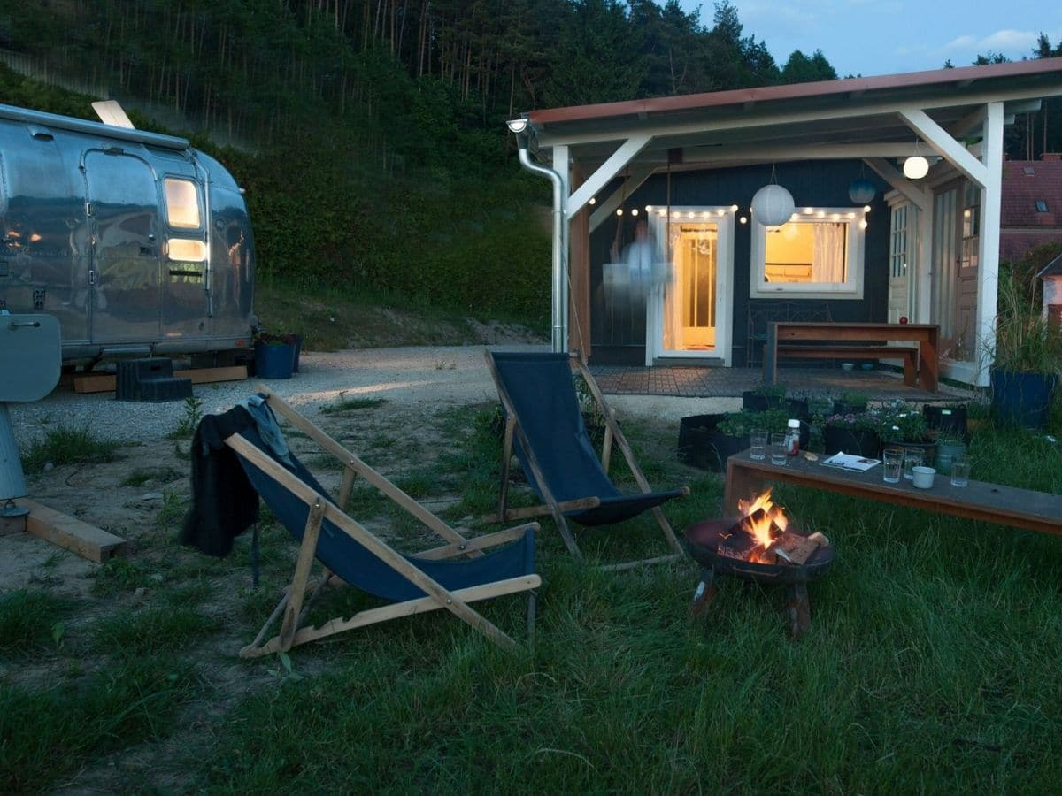 Empty blue chairs in yard by fire pit in front of blue tiny house