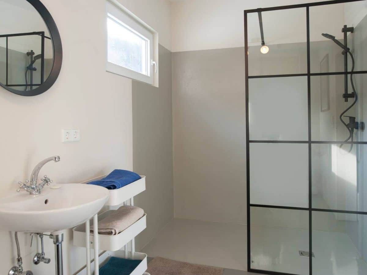 Gray shower wall with black frame and glass opening against white walls