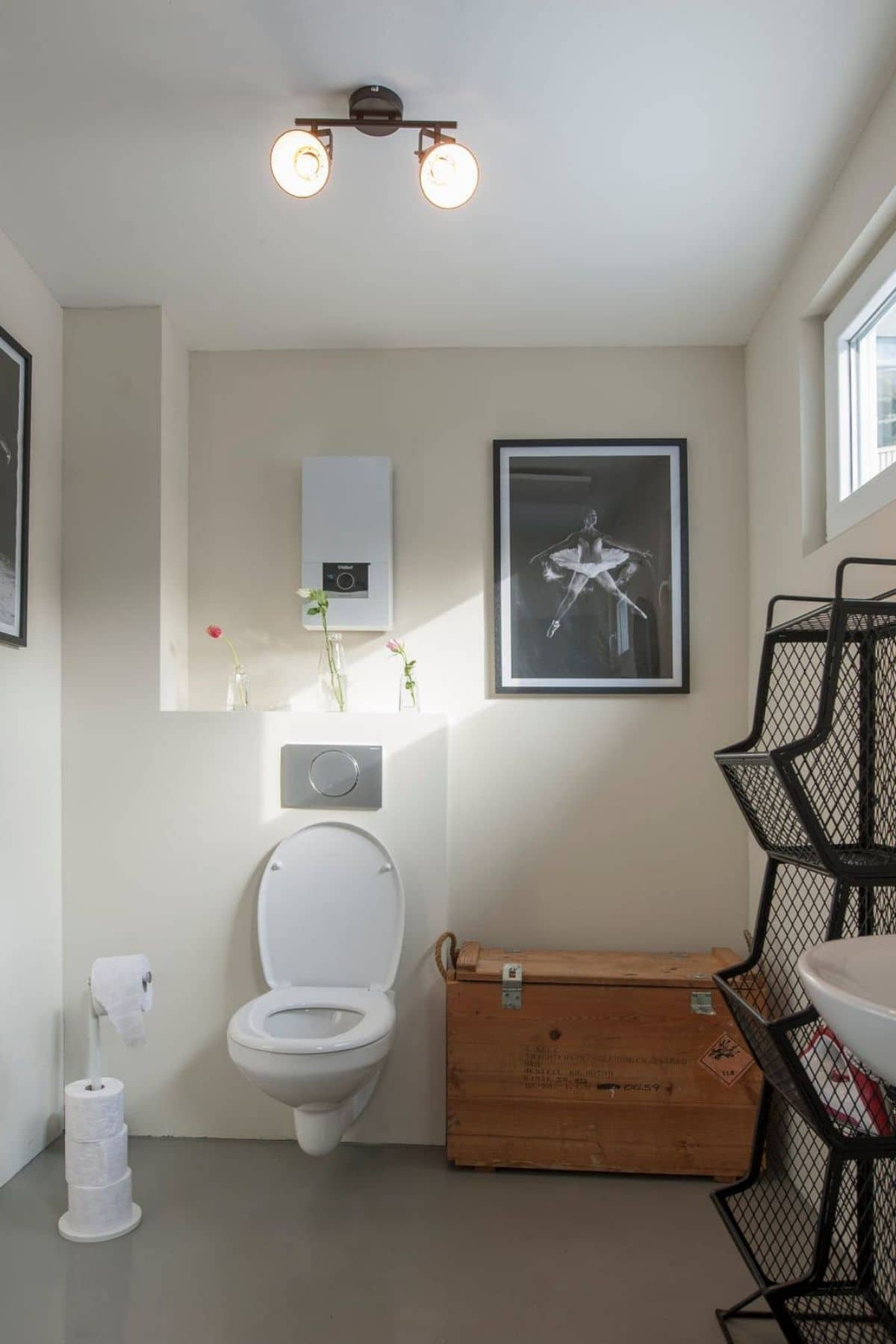 Toilet with lid up mounted on white wall next to blonde wood trunk