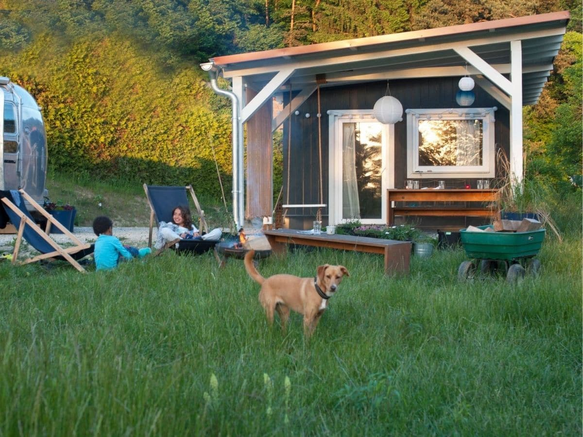 Woman in chair in front of tiny home porch by dog in yard