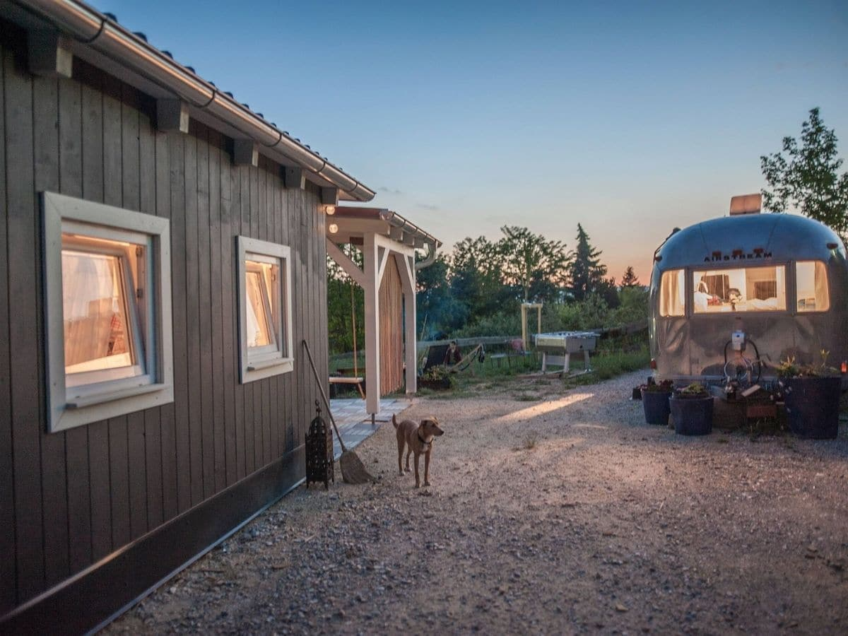 Side of tiny house by driveway with airstream trailer in background
