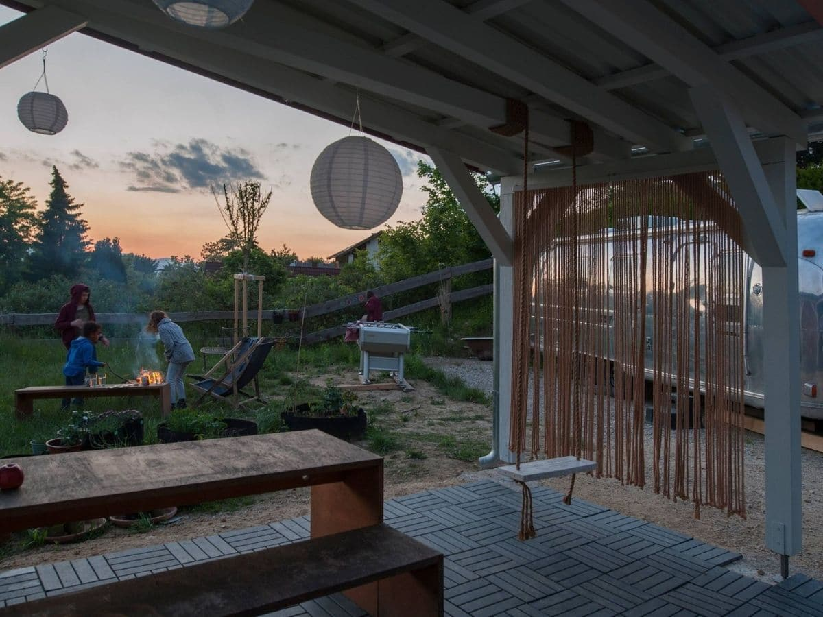 Porch with wooden picnic bench and paper lantern hanging from ceiling