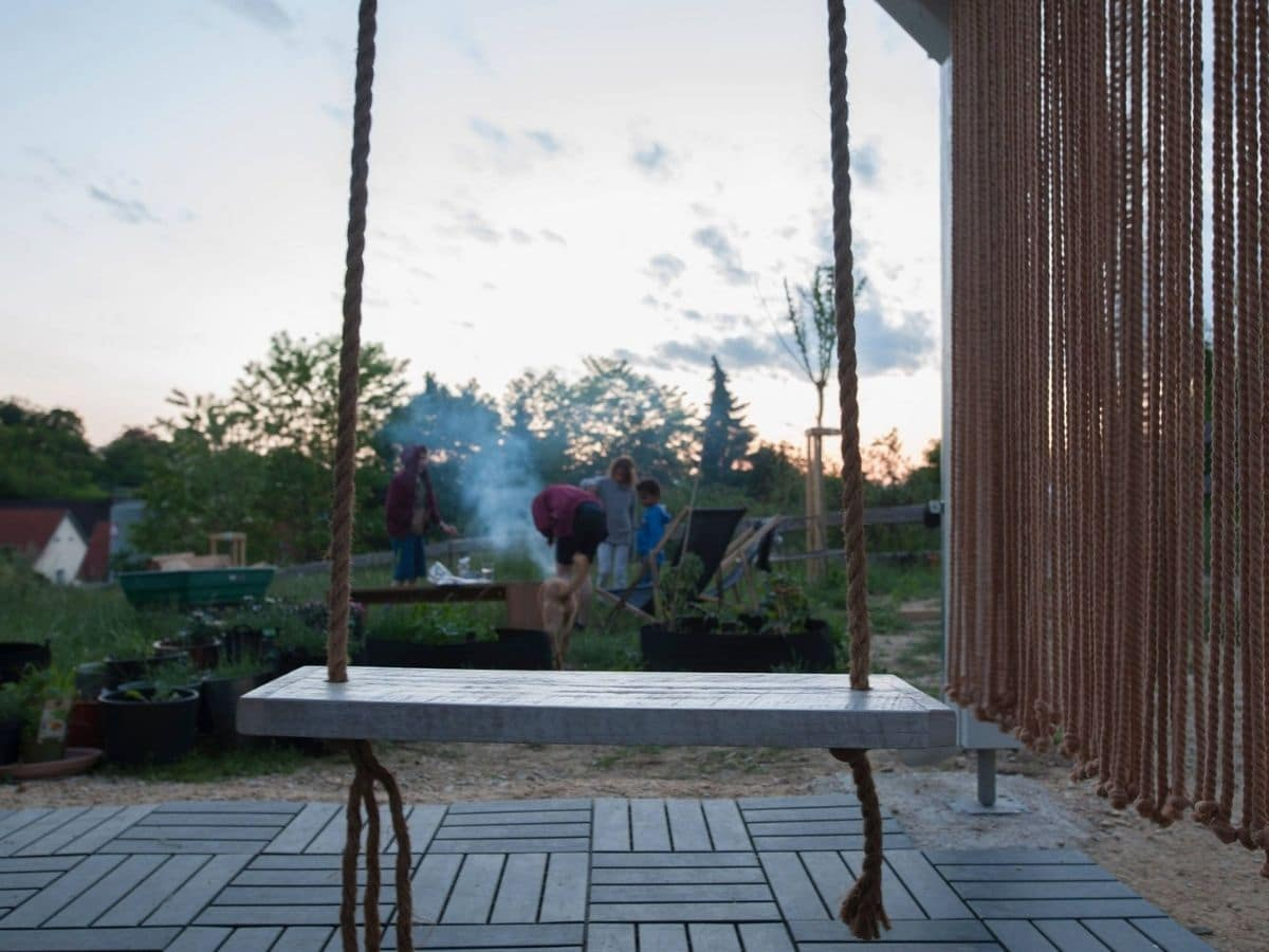 Swing of wood slat and rope on porch with view out at people in yard
