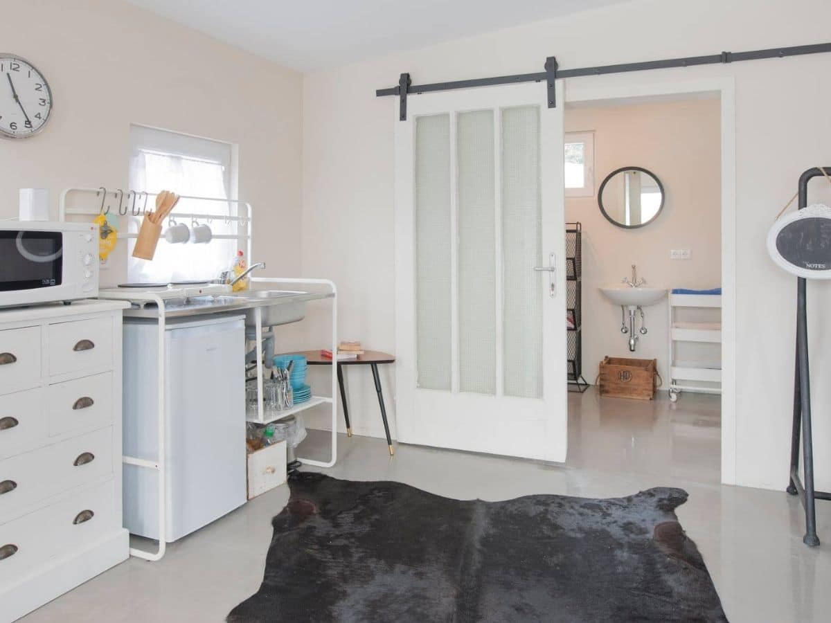 Frosted glass barn door against wall to bathroom by gray area rug