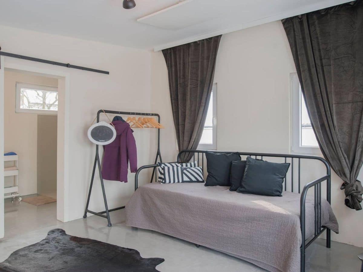 Black matte metal futon against wall with dark curtains behind it