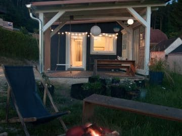 Blue tiny house with white trim and large porch by small fire pit