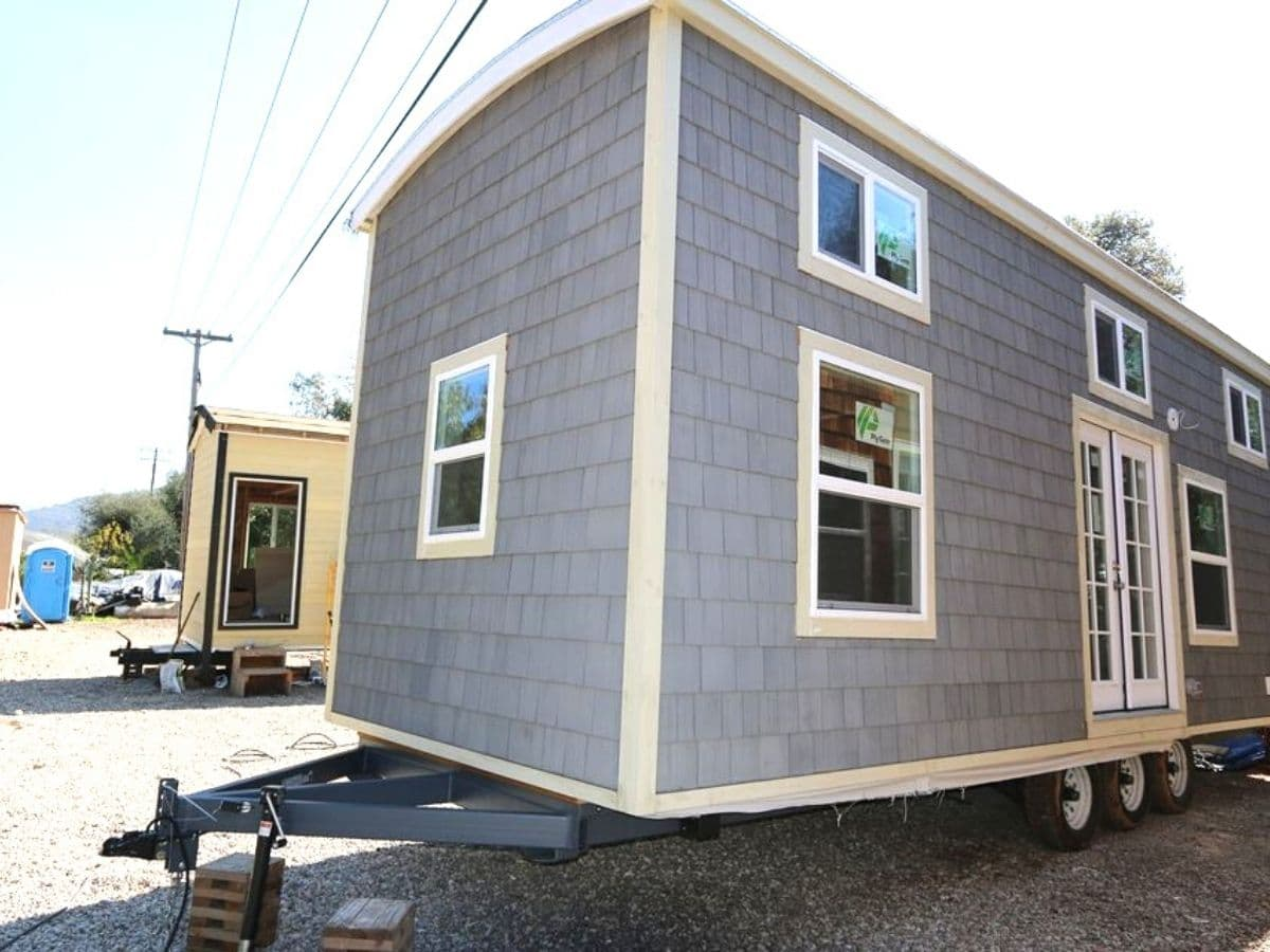 Side of tiny home on lot with white trim on light gray siding