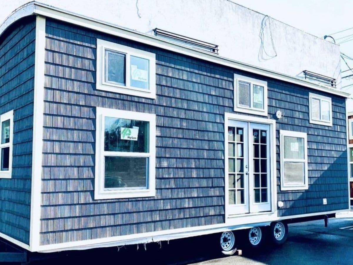 Exterior of tiny home with dark gray siding and white trim