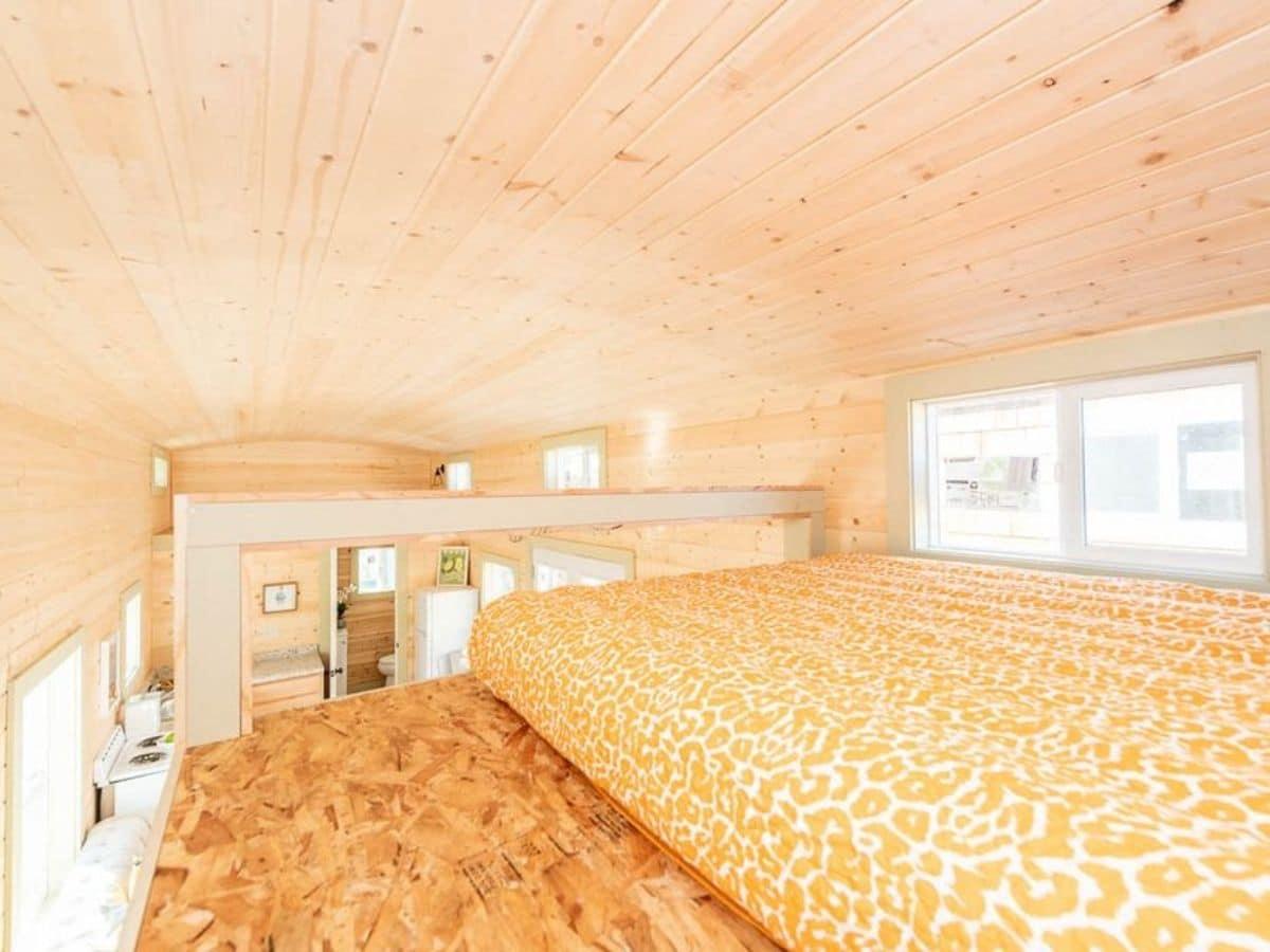Yellow blanket on mattress in tiny house loft