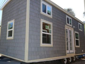 Gray tiny house with white trim on lot