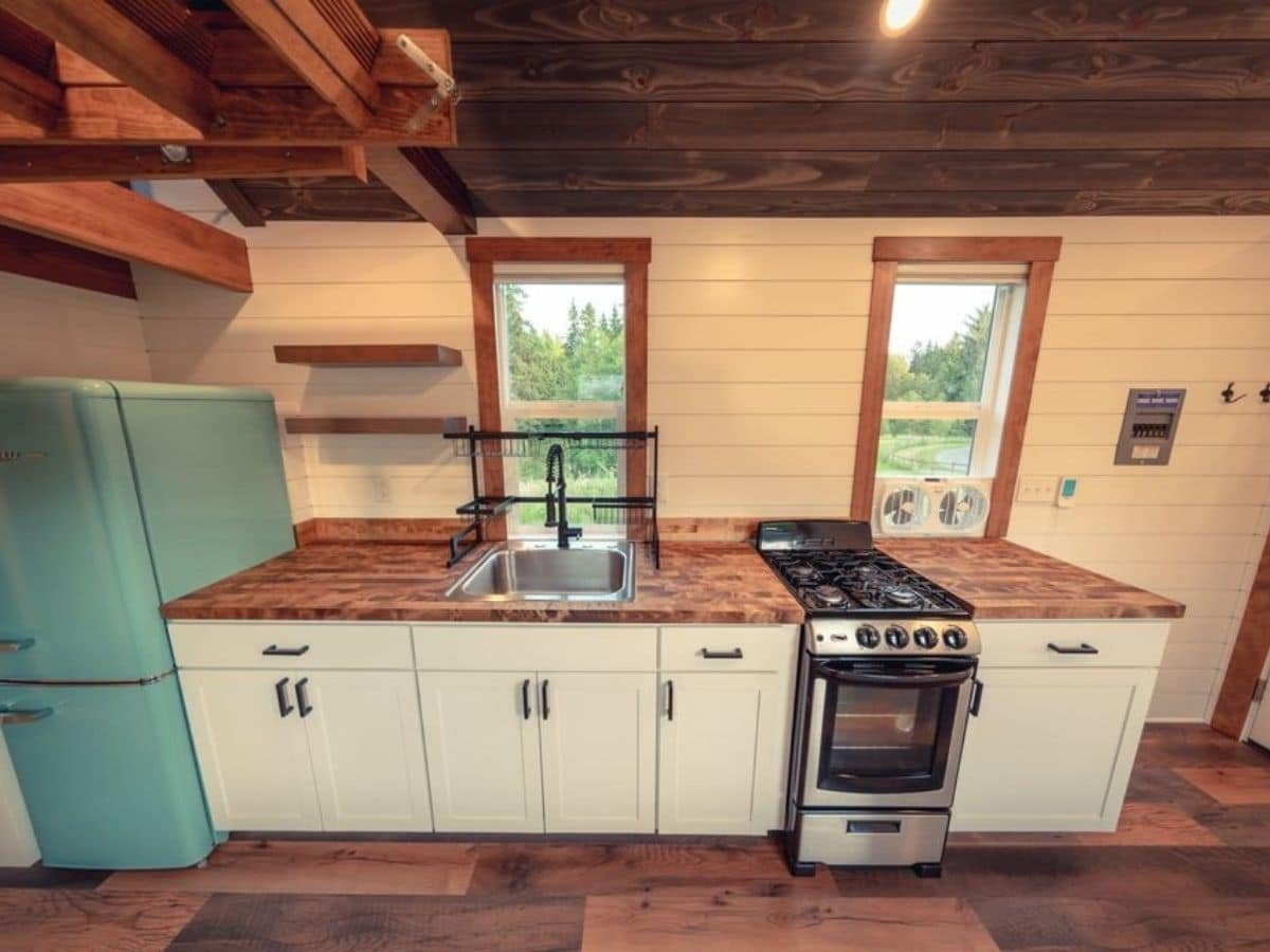 White kitchen counter with stove sink and light teal refrigerator