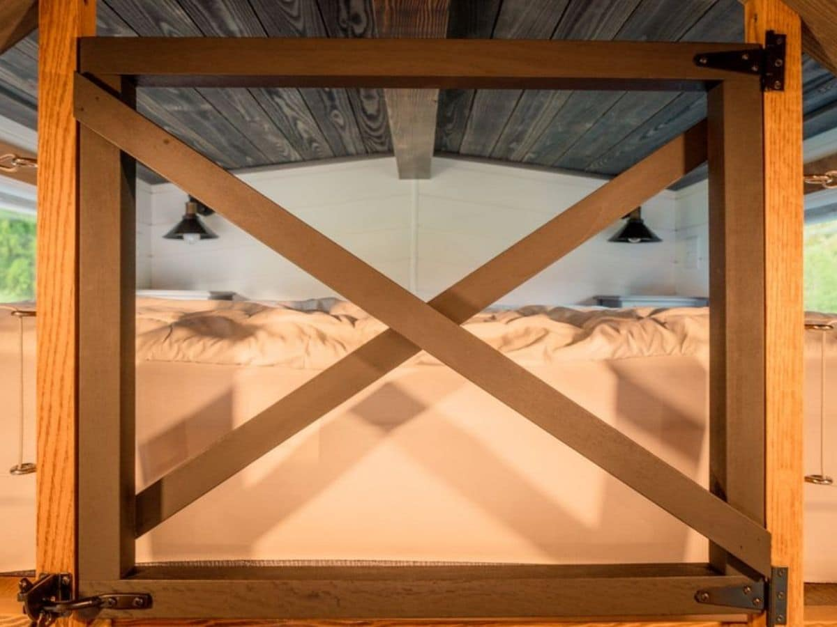 Wooden gate in front of bed in loft space