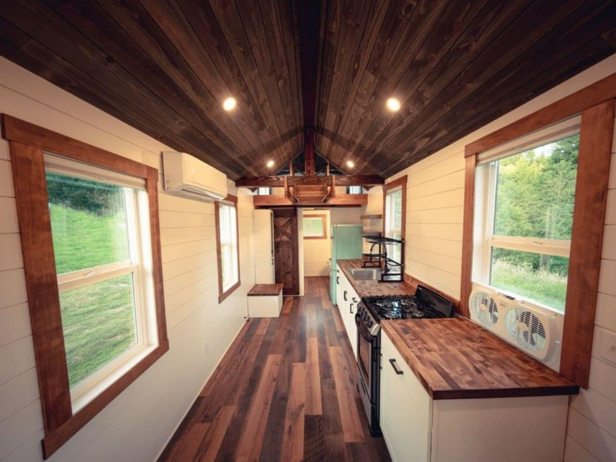 Interior of tiny home with dark wood floor and white shiplap walls