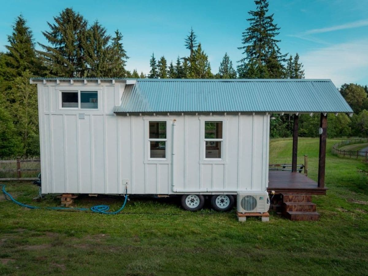 Side of white tiny house on wheels in gass field
