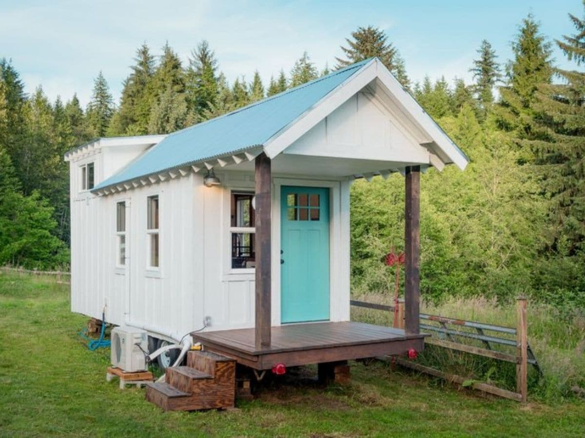 Side of white tiny house with teal roof and dark wood porch