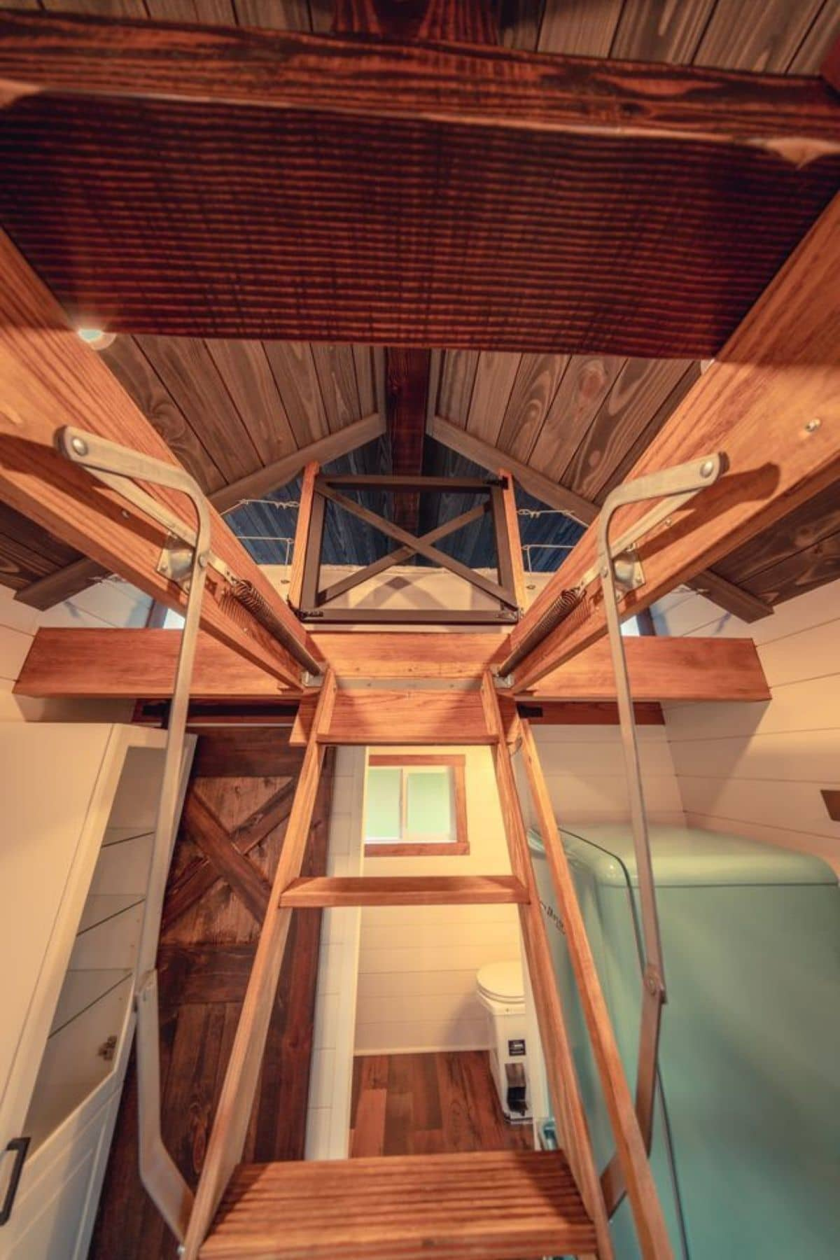 View looking up ladder to loft in tiny home with dark wood trim