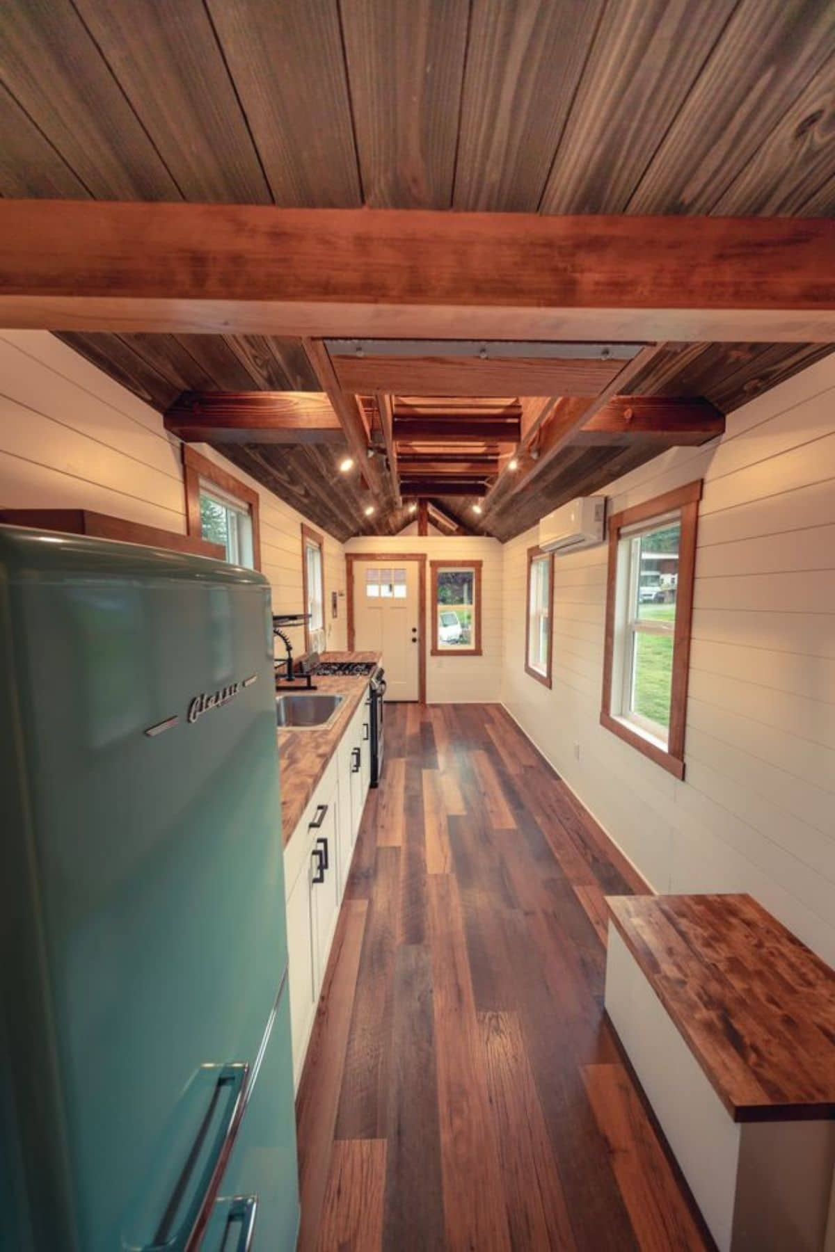 View from ptiny house bathroom toward front door of home with dark wood floor and ceiling