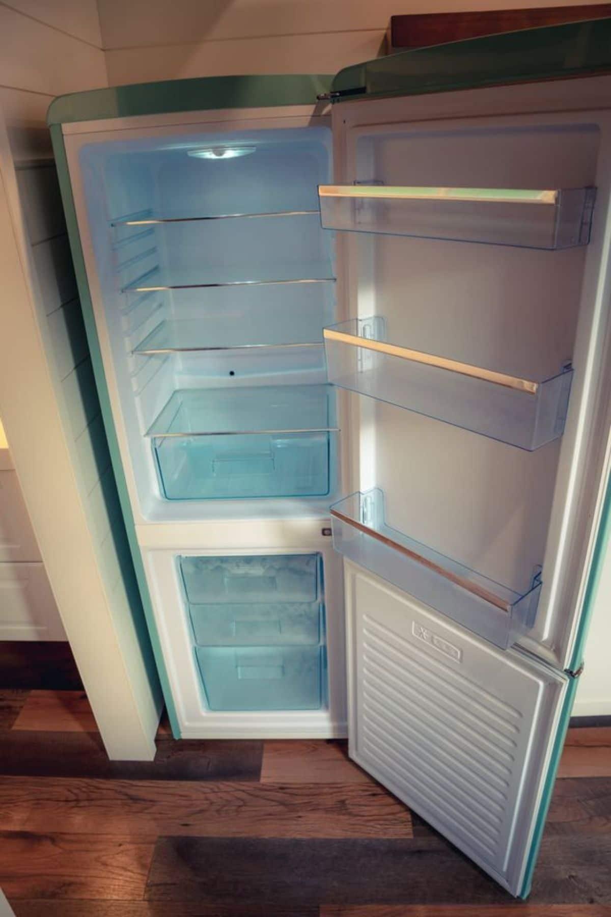 Retro teal refrigerator open door with plastic bins