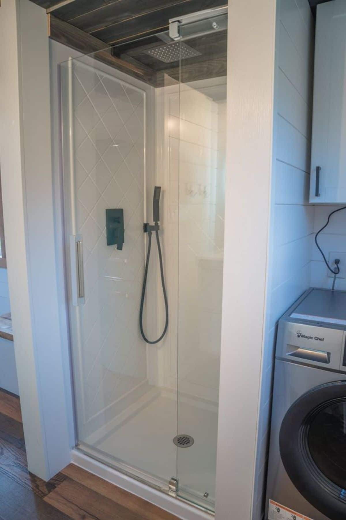 Tall white shower stall in corner with glass door