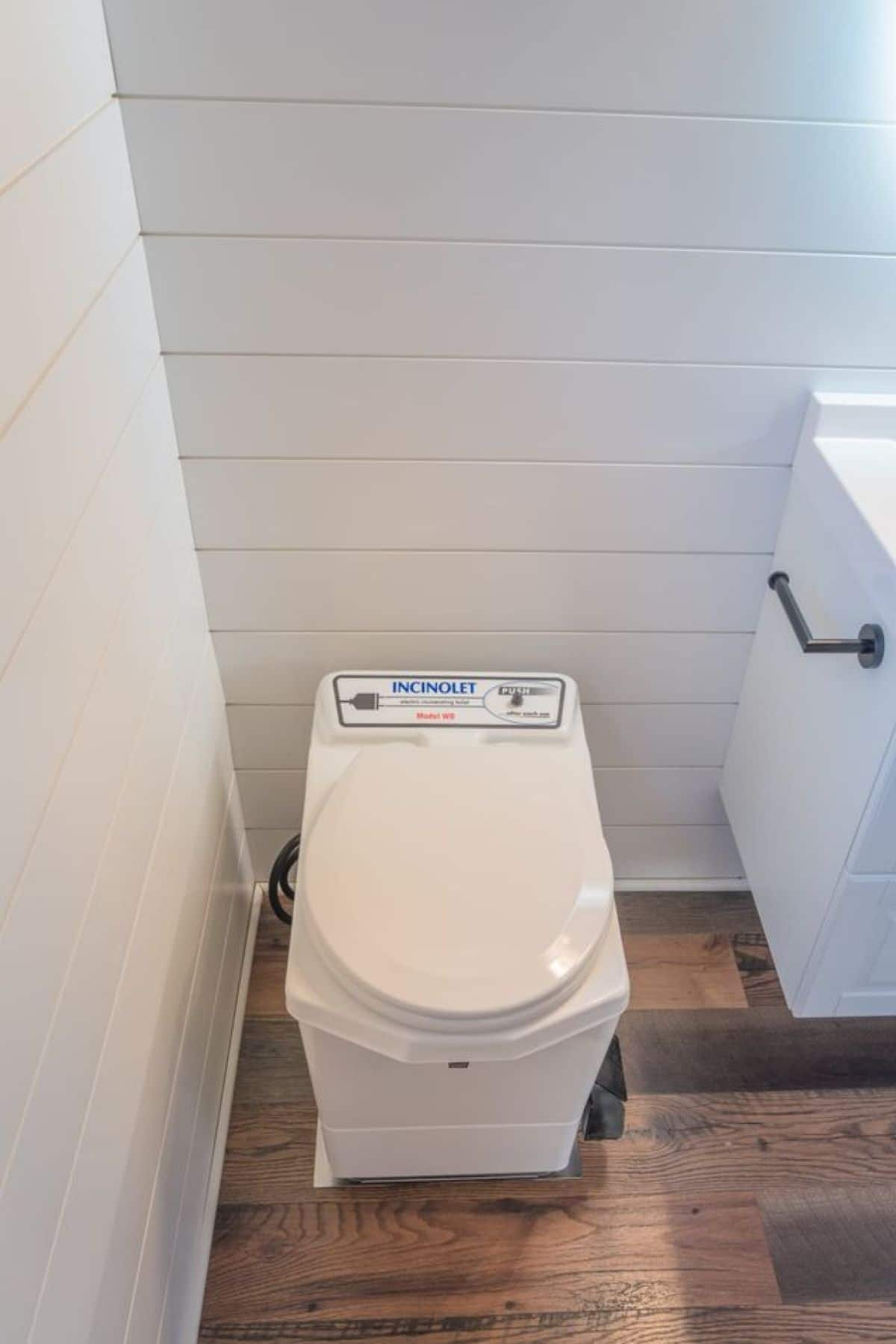 Compost toilet against white shiplap wall by white vanity