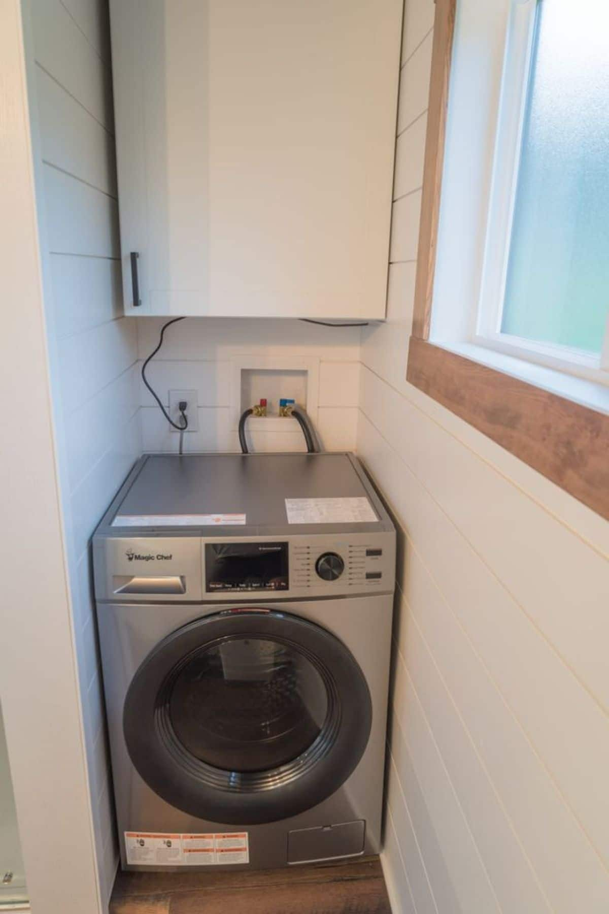 Combination washer and dryer below white cabinet tucked into corner by window