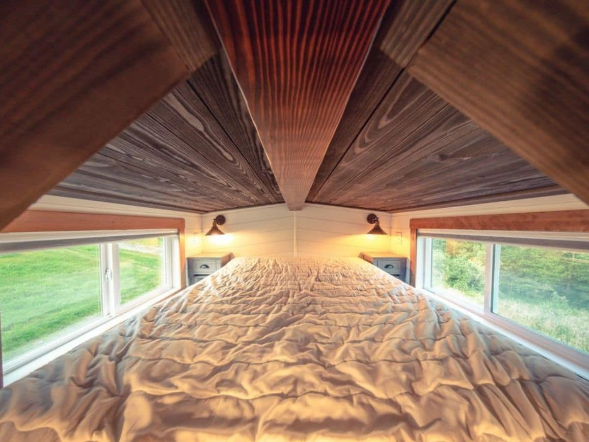 View into tiny home loft with light gray bedding and gray bedside tables on both sides