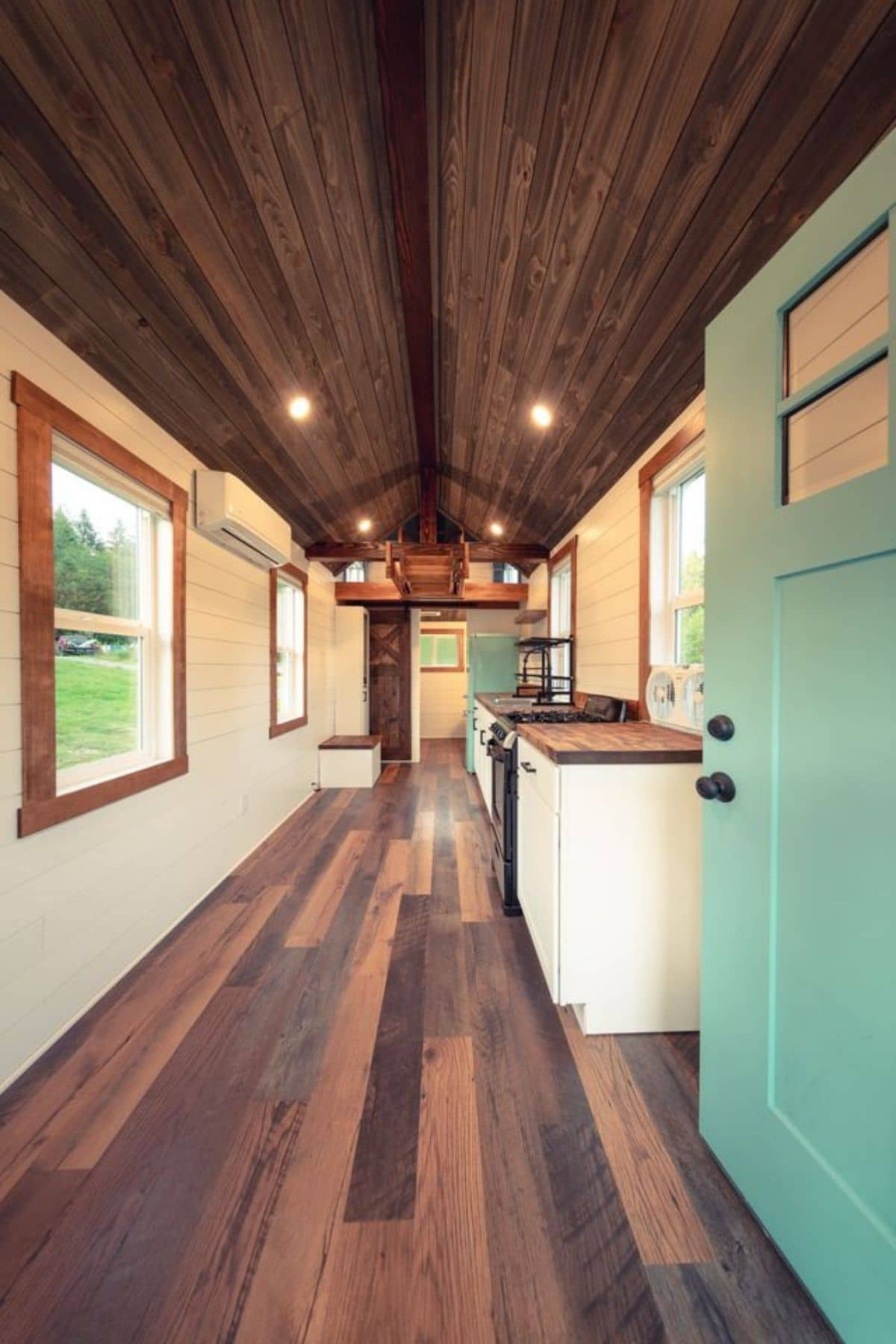View just through light teal door on right showing white walls and dark wood floors