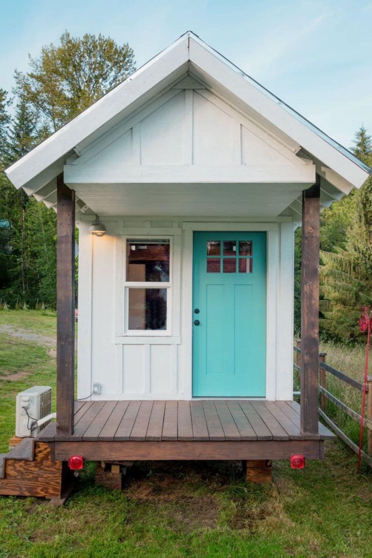 Front of white tiny home with dark wood porch and teal door