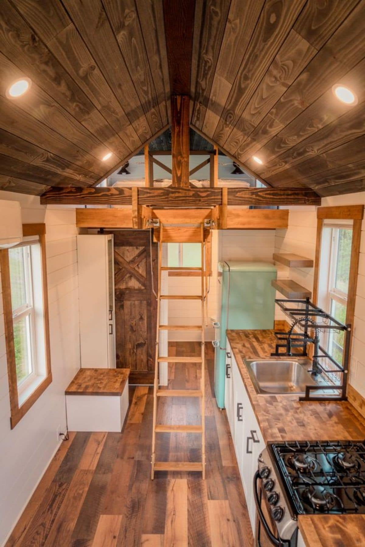 View of interior tiny home with dark wood stained floors and kitchen counter on right