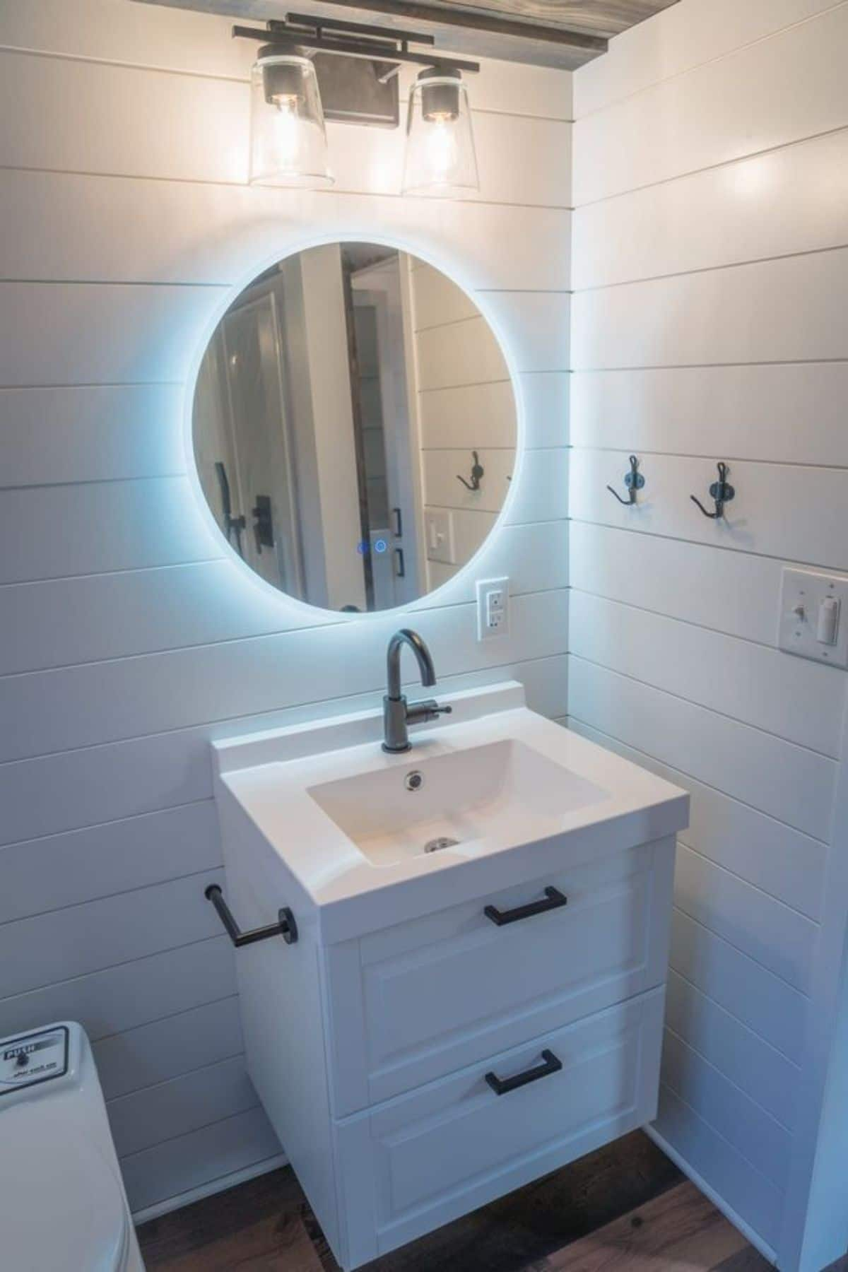 Round lit mirror on wall above small white vanity