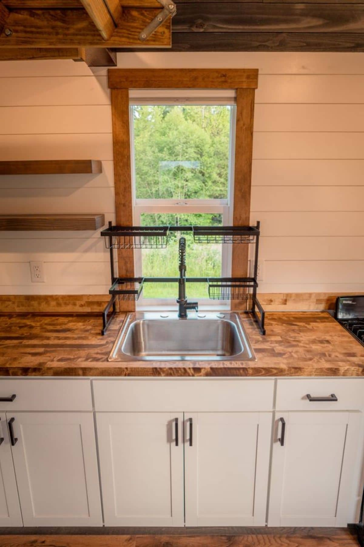 Stainless steel sink in front of window with black matte rack above