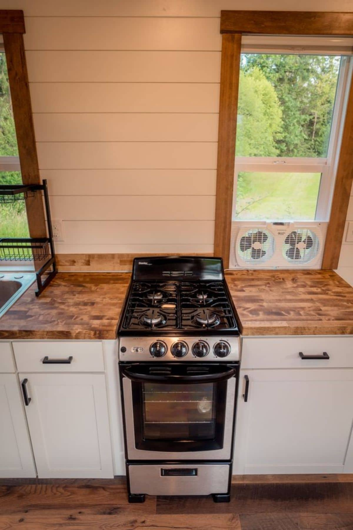 4 burner gas stove inside white cabinets with butcher block countertops