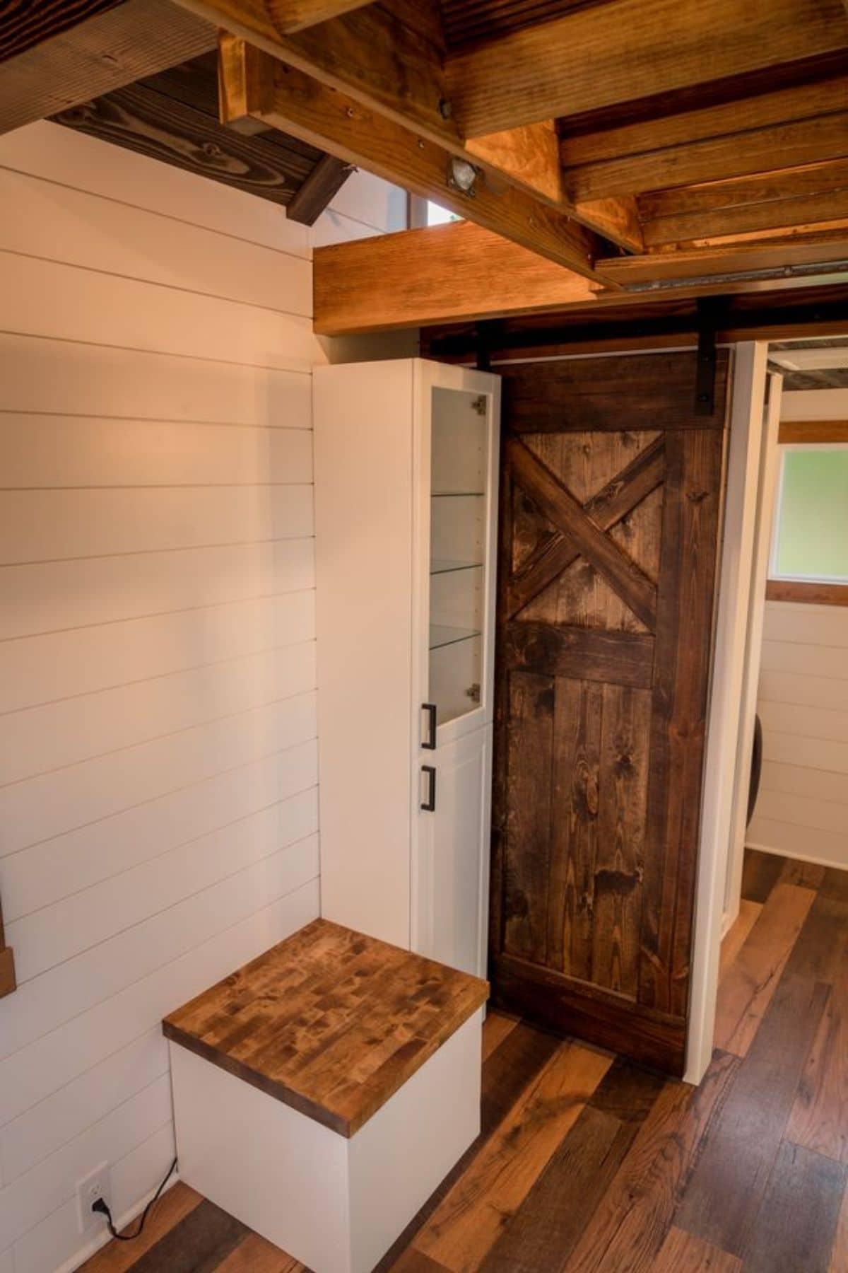 White cabinet next to dark wood barn door on white shiplap wall