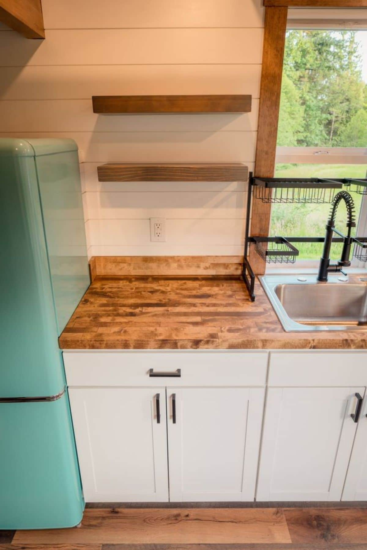 White cabinet with butcher block counter next to teal refrigerator