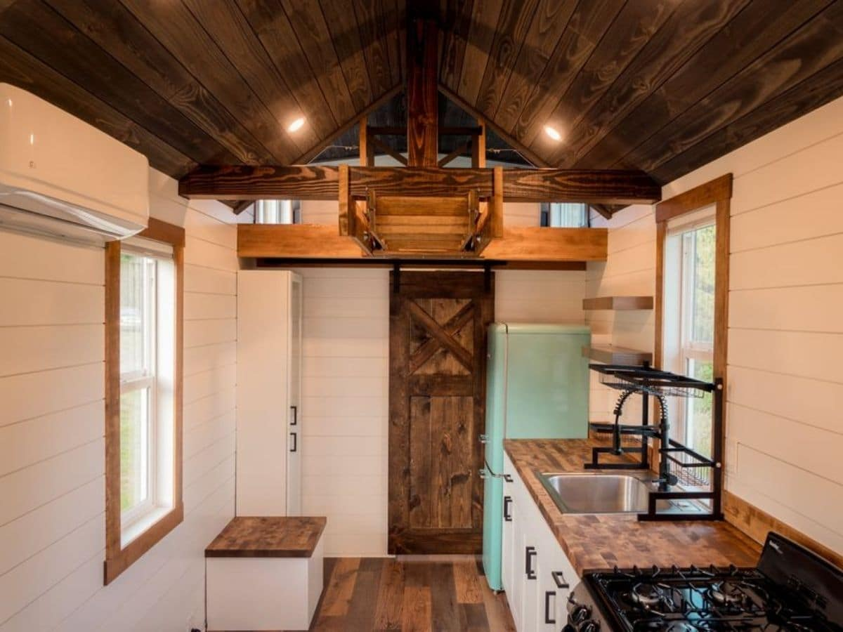 Dark stained wood barn door at end of hall in white tiny home with loft above door