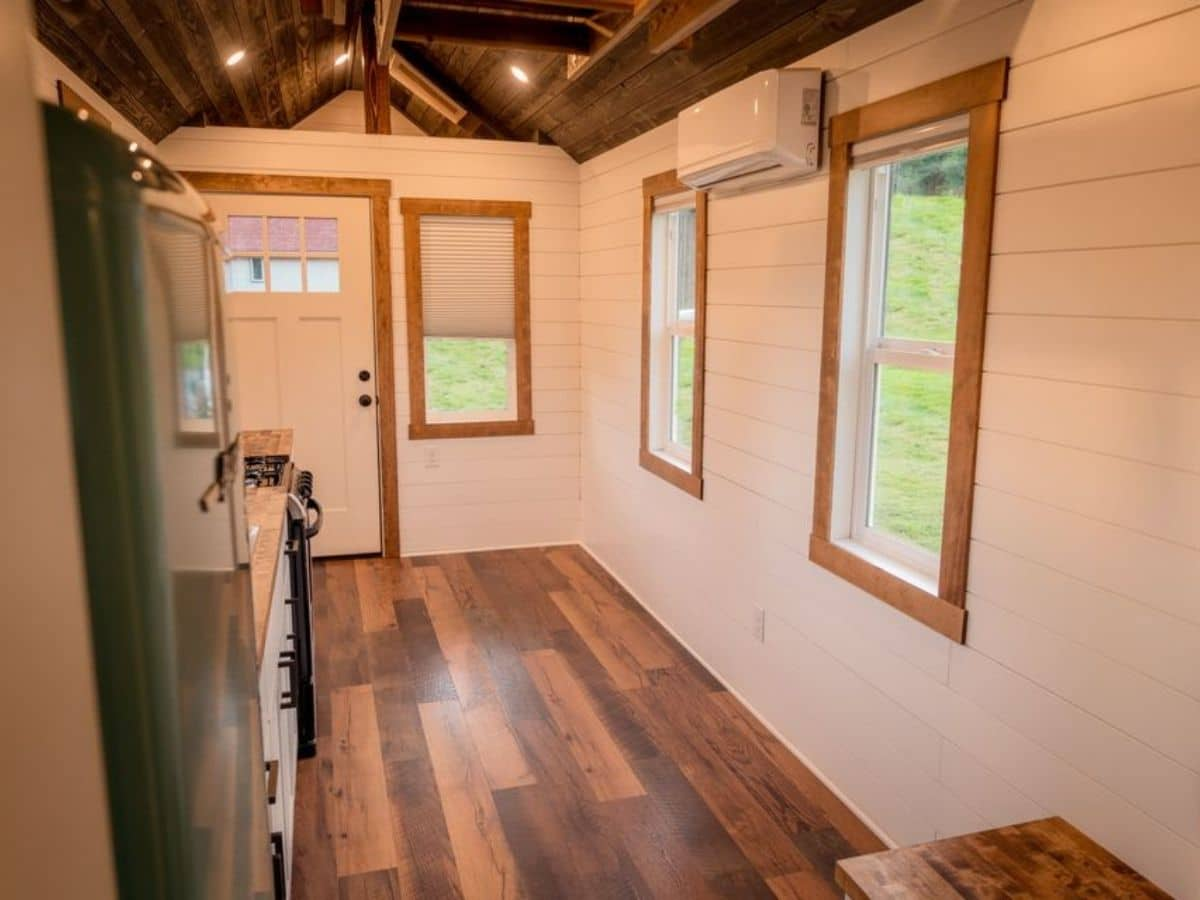 Open front living space with three windows and white shiplap walls